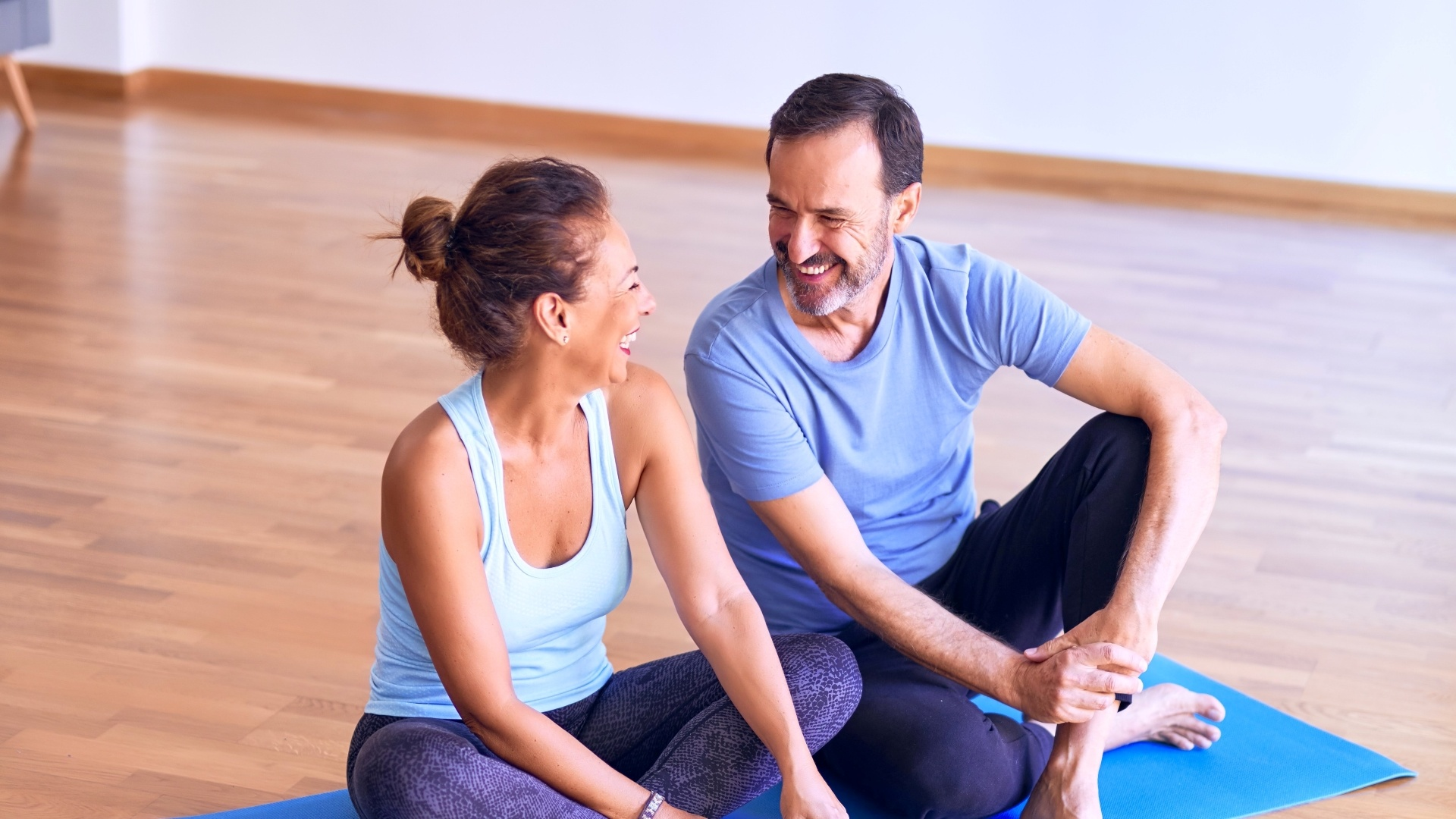 happy middle aged couple doing couples yoga during covid-19 pandemic